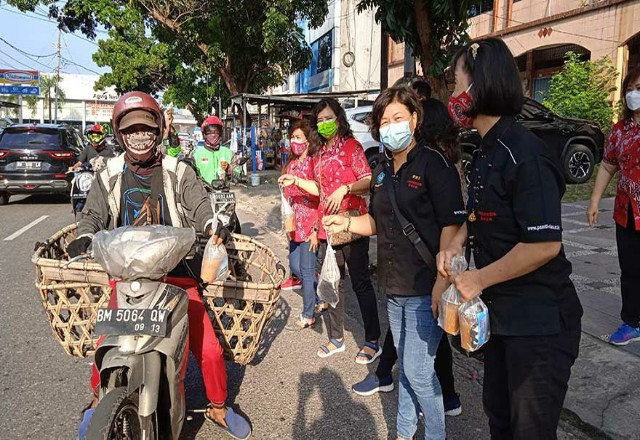 Perwanti dan PSMTI Riau bagi-bagi takjil ke pengendara.