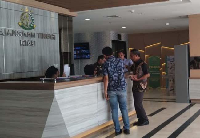 Syafril didampingi stafnya ketika menyerahkan tanda pengenal ke bagian penerimaan tamu di gedung Kejati Riau usai pemeriksaan, Kamis (20/2/2020) sore.