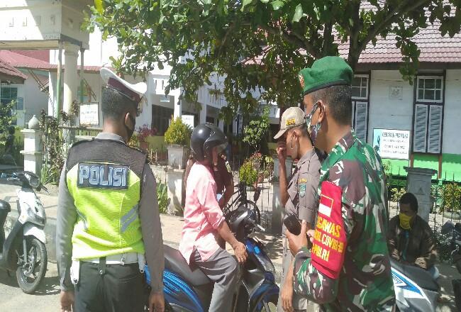 Petugas gabungan memberikan pengarahan ke warga pengendara yang tidak mengenakan masker, saat hari pertama operasi yustisi penegakan hukum protokoler kesehatan Covid-19.