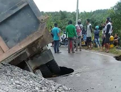Truk nyemplung ke sungai karena jalan amblas.