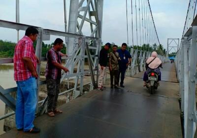 Plt Kadis PUPR Kuansing Ade Fahrer didampingi Kabid Bina Marga Jafrison turun meninjau kondisi jembatan gantung.