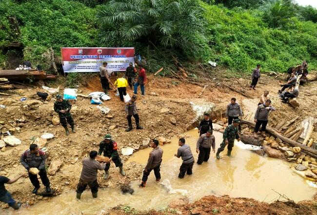 Personel polisi dari Polres Rohul bahu membahu bersama TNI membuat sekat kanal dengan memanfaatkan batang pohon tumbang, pasir dan bebatuan.