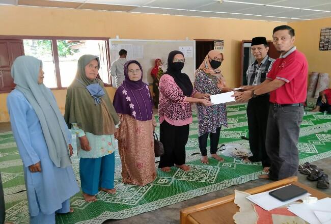 Ketua harian Ikatan Keluarga Magek (IKM)  pekanbaru, Ali Fahmi pakai peci dan Sekretaris IKM Imrizal serta Tim tanggap darurat Covid-19 menyarahkan zakat mal.