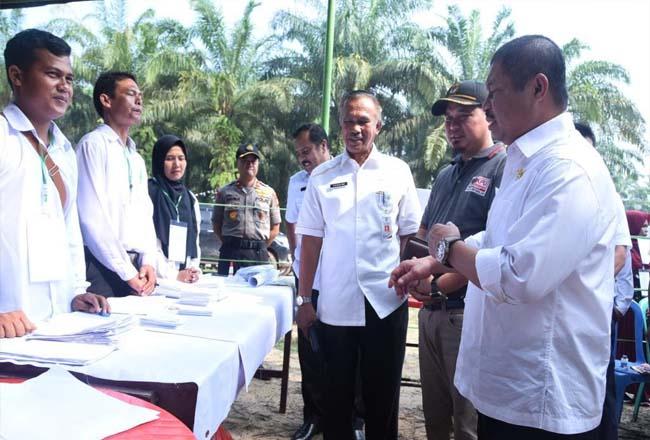 Bupati Amril didampingi Ketua KPU Bengkalis saat meninjau pemungutan suara di TPS 01 Desa Harapan Baru.