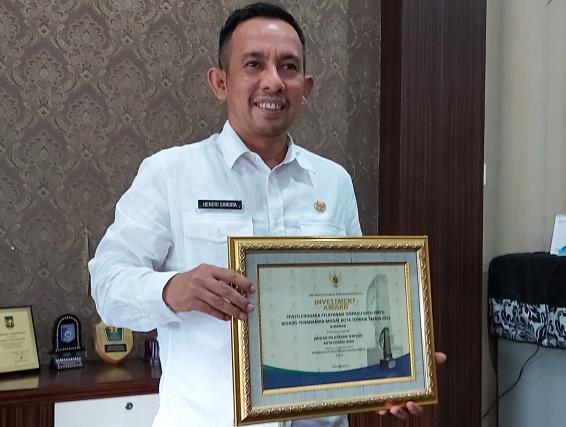 Hendri Sandra Kepala DPM-PTSP Kota Dumai memegang penghargaan Investment Award dari Badan Koordinasi Penanaman Modal (BKPM) RI.