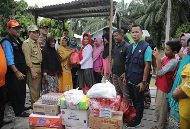 Bupati Sukiman dan ketua PMI Rohul Hj Peni Herawati, salurkan bantuan korban banjir di Desa Kasang Mungkal, Bonai Darussalam.