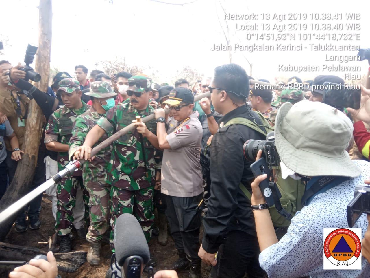 Panglima TNI dan Kapolri sedang memadamkan kebakaran lahan di Kabupaten Pelalawan