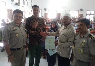 Kades sontang didampingi Kepala BPN Rohul, serahkan sertifikat tanah program PTSL ke perwakilan masyarakat.