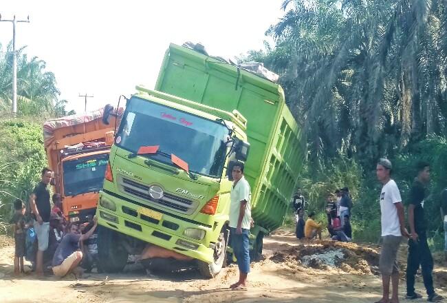 Dua tronton terjebak di jalan rusak, mengakibatkan kemacetan panjang di Jallinprov Mahato, sementara jalan baru diperbaiki secara swadaya.