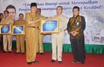 Bupati Indragiri Hilir HM Wardan saat menerima Piagam Opini WTP dari Gubernur Riau.
