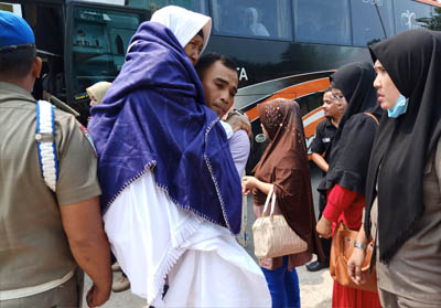 Jemaah Haji tertua digendong anaknya saat bus yang membawa rombongan haji Dumai tiba di halaman MAsjid Al-Manan Bagan Besar.