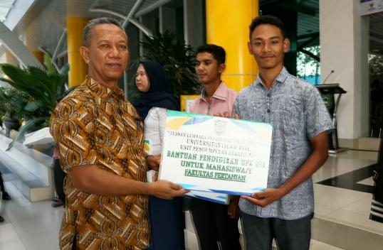 Rektor UIR Syafrinaldi menyerahkan bantuan pendidikan UPZ kepada mahasiswa.