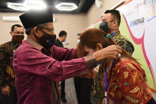 Kepala Dinas Pemuda, Olahraga dan Pariwisata Kota Dumai H. Syamsuddin memakaikan tanda peserta pelatihan Management Homestay kepada salah satu peserta.