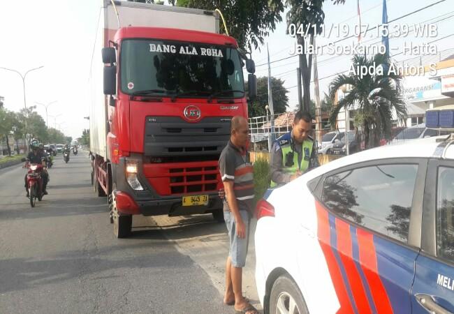 Petugas saat membuat surat tilang pada truk.