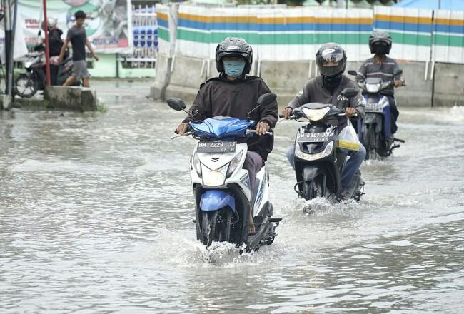 Kendaraan bermotor menerobos genangan air saat melintas di Jalan Ahmad Dahlan, Kota Pekanbaru. Foto: Riaupos