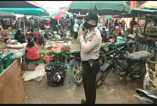 Aparat Kepolisian saat mensosialisasikan new normal ke pasar.
