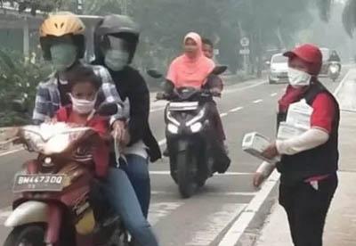 Relawan PMI Provinsi Riau membagikan masker gratis kepada pengguna kendaraan untuk mengantisipasi terjangkitnya penyakit yang disebabkan kabut asap akibat kebakaran hutan dan lahan (karhutla). FOTO: PMI Provinsi Riau