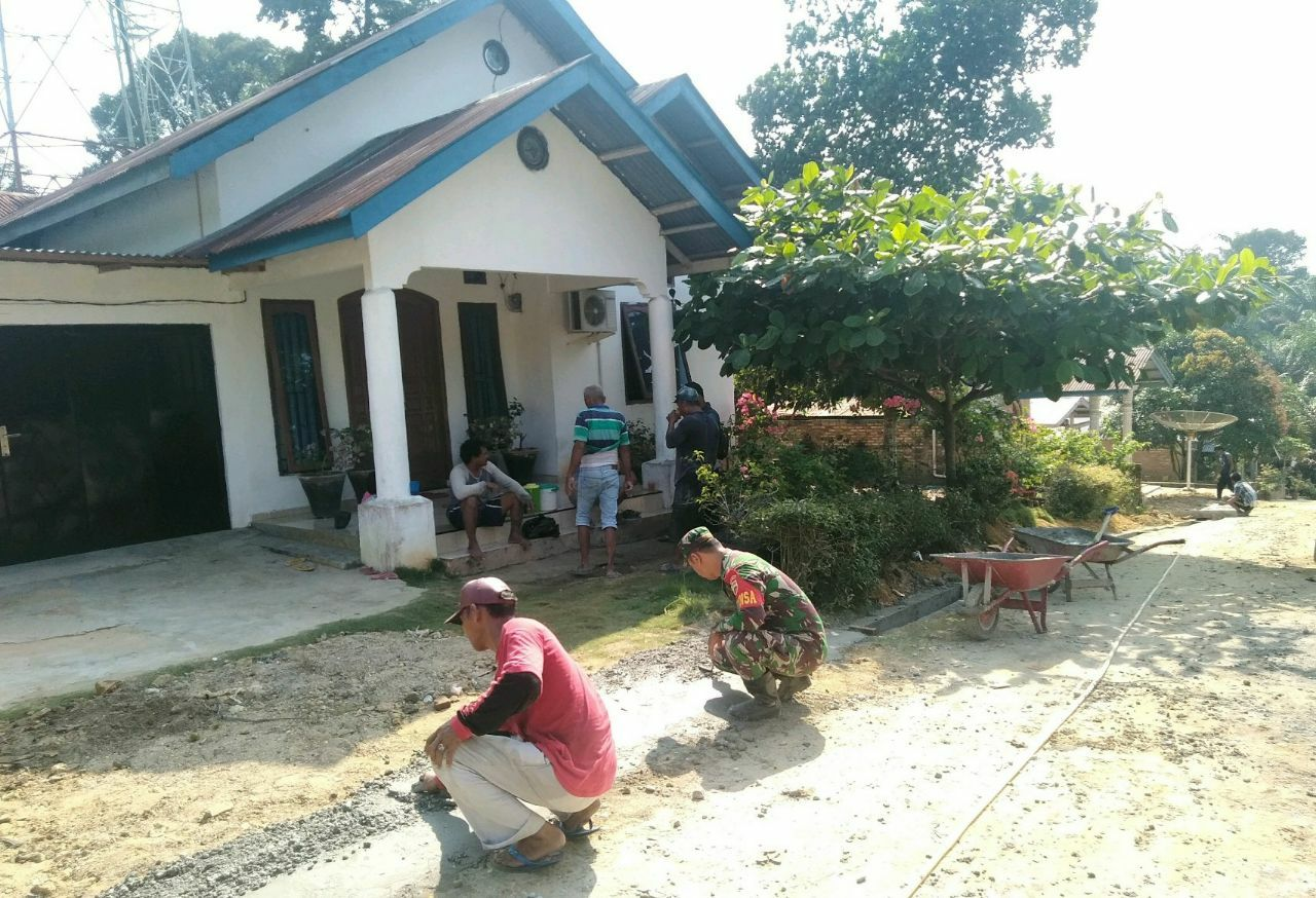 Babinsa Koramil 09/Langgam dan warga membangun drainase di sisi jalan pemukiman warga.