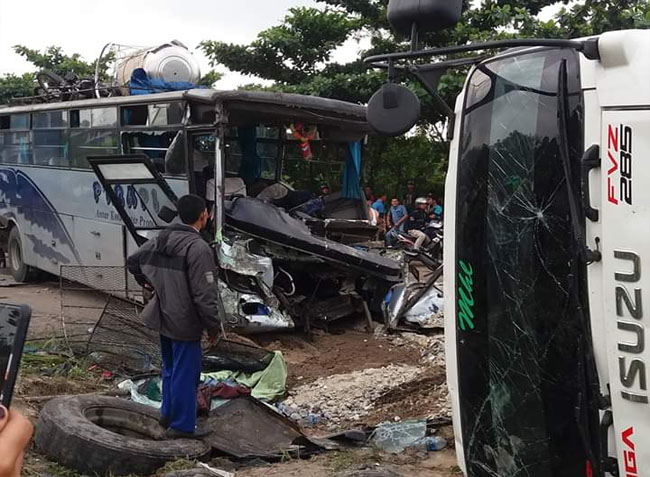 Bus Rapi dan truk fuso terbalik di jalan.