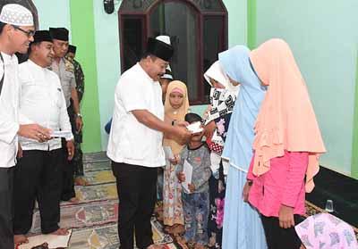 Asisten Prekonomian dan Pembangunan Setda Bengkalis, Heri Indra Putra menyerahkan santunan.