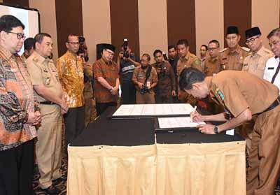 Kadis Kominfotik Bengkalis, Johansyah Syafri ketika menandatangani Komitmen Bersama di hadapan Wakil Gubernur Riau dan Ombudsman RI, Selasa, 21 Mei 2019.