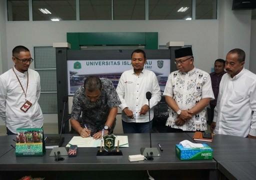 Wakil Rektor III Ir Rosyadi menandatangani MoU UIR dengan Telkomsel, disaksikan Wakil Rektor I Dr H Syafhendry