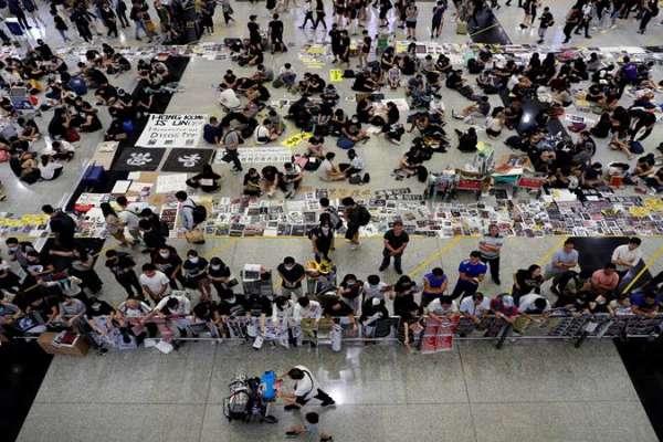 Para pemrotes RUU Anti-Ekstradisi membagikan selebaran kepada para penumpang selama demonstrasi massa di bandara internasional Hong Kong, di Hong Kong, China, 13 Agustus 2019. FOTO: Reuters