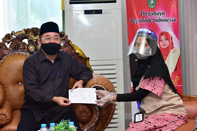 Plh Bupati Bengkalis Bustami HY usai melakukan coklit data Pilkada di kediamannya.