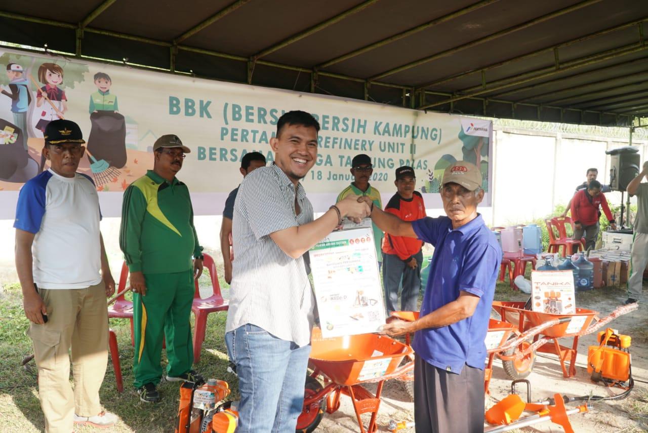 Didi Andrian Indra Kusuma Unit Manager Comm., Relations & CSR Pertamina RU II menyerahkan bantuan mesin potong rumput kepada warga Tanjung Palas.