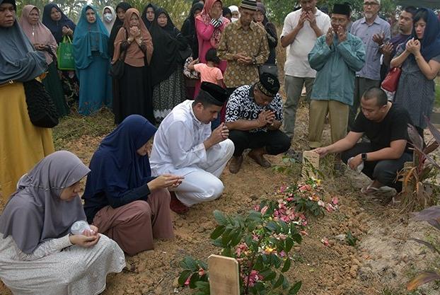 Sejumlah keluarga dan pelayat berdoa pada pemakaman Helmy Oemar di Tempat Pemakaman Umum Kertama, Kota Pekanbaru, Riau, Minggu (25/8/2019).