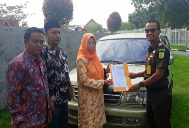 Kasi Perdata Tata Usaha Negara Kejari Rohul, Roni Saputra SH, menerima penyerahan mobil dinas milik Pemkab Rohul yang sempat 10 tahun tak dikembalikan pensiunan PNS disaksikan pihak BPKAD Rohul.