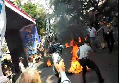 Anggota polisi terbakar di tengah aksi demo. FOTO: Merdeka.com