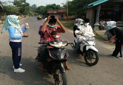Petugas kesehatan membagikan masker kepada pengguna jalan.