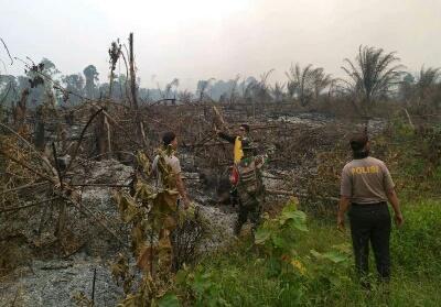 Anggota Polsek Kuantan Mudik bersama Koramil Kuantan Mudik tengah berada di lahan yang terbakar.