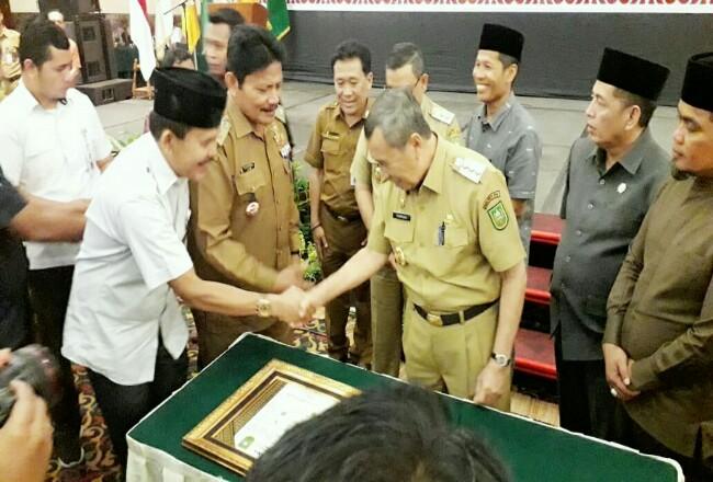 Gubernur Riau Drs H Syamsuar, Msi menyalami Ketua KI Riau Zufra Irwan,SE. Foto: MataPers