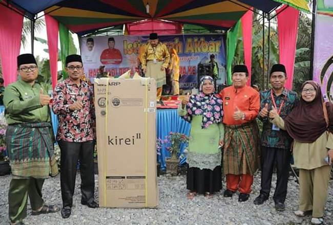Bupati Sukiman, mebagikan hadiah kepada pemenang doorprize saat menghadiri Hari Jadi ke - 21 Desa Bencah Kesuma