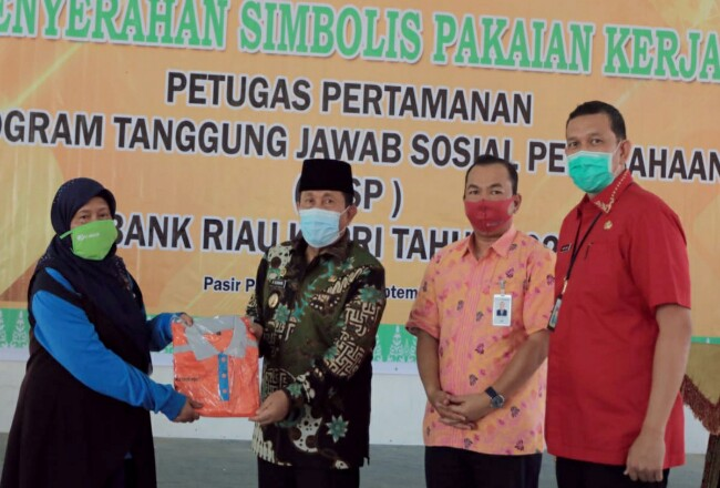 Bupati Sukiman, secara simbolis serahkan bantuan pakaian ke seorang petugas kebersihan taman, disaksikan pimpinan PT BRK Pasir Pangaraian dan Kadistarcip Herry Islami.