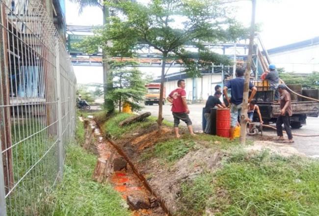 Tumpahan minyak milik PT Ivo Mas Tunggal di area parit PT Pelindo, Kota Dumai, dibersihkan petugas. FOTO: Dok.