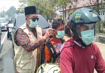 Kepala BPBD Rohul, ikut membagikan masker gratis ke pengendara di jalan raya kawasan Taman Kota, Pasir Pangaraian.