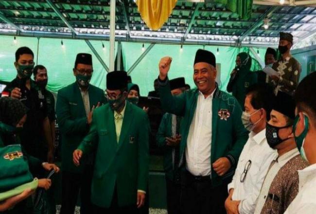 Zulkarnain Kadir mengacungkan tangan usai dipasangkan jaket PPP di harlah ke 48 PPP di Bangkinang, Kampar pada Sabtu (16/1/2021). Foto: Tribunpekanbaru