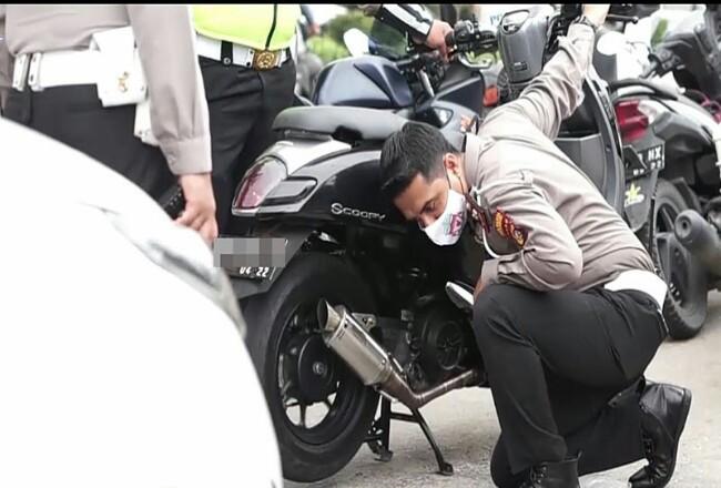Petugas Satlantas Polresta Pekanbaru mengecek suara knalpot kendaraan yang sudah dimodifikasi, Minggu (12/7/2020). Foto: Riaupos