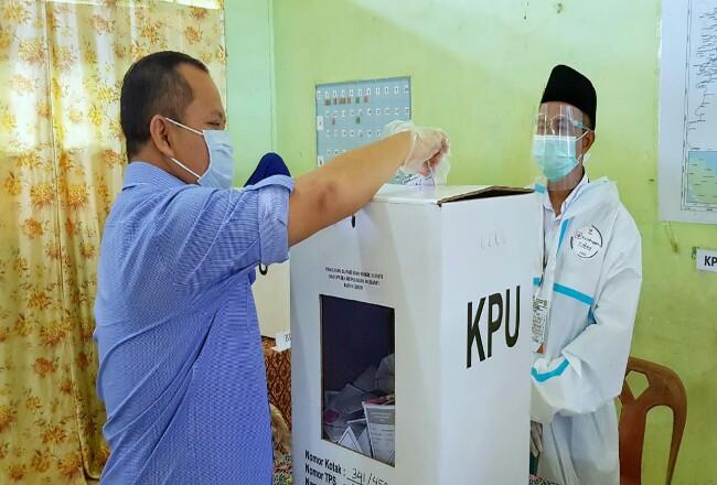 Bupati Kepulauan Meranti, Drs H Irwan saat memasukkan surat suara usai mencoblos.