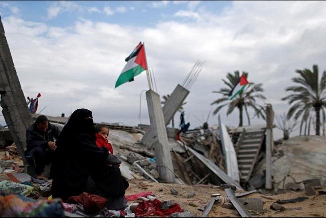 Wanita Palestina berkumpul di dekat rumahnya yang hancur