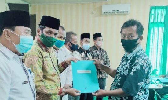 Kepala Kantor Kemenag Rohul Syahruddin menyerahkan sertifikat halal kepada pelaku UMKM.