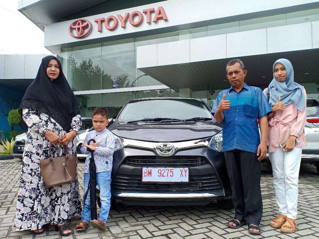 Bustami dan Lindawati bersama kedua anaknya berfoto di depan Calya miliknya