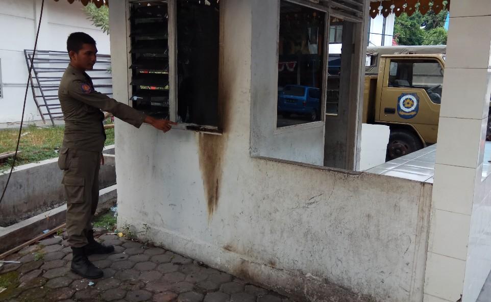 Personel Satpol PP Pekanbaru perlihatkan bekas terbakar di pos jaga akibat dilempar molotov orang tak dikenal.