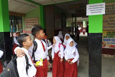 Pihak sekolah di SDN 022 Dumai memasang pengumuman merumahkan pelajar akibat kabut asap. FOTO: Bambang