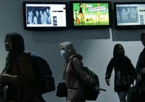 Petugas memantau suhu tubuh para penumpang menggunakan alat pemindai di Terminal Kedatangan Internasional Bandara Internasional Soekarno Hatta, Tangerang. Foto: CNNIndonesia