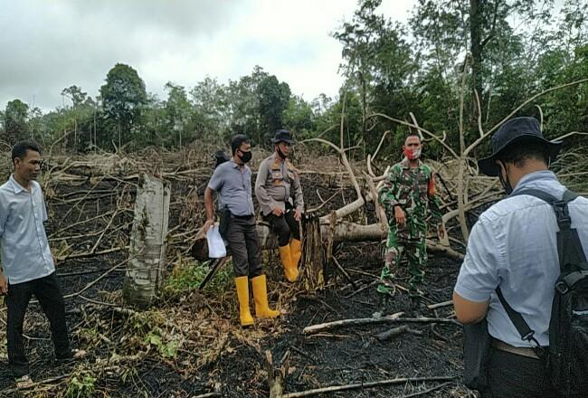 Kapolsek Rambah Iptu P Simatupang bersama personel gabungan TNI, turun mengecek dan pasang garis Polisi di lahan warga yang diduga dibakar, di Dusun Pawan Desa Rambah Tengah Hulu, Kecamatan Rambah.