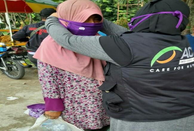 Ketua MRI ACT Deli Serdang,Pristia Wati sedang memasang masker kepada seorang ibu yang sedang berada di seputaran Lapangan Merdeka Medan.